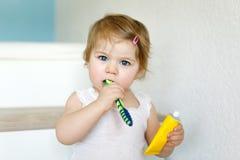 拿着牙刷和刷第一颗牙的小女婴 学会的小孩清洗乳齿 图库摄影
