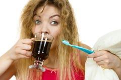 拿着牙刷和咖啡的愉快的妇女 免版税库存照片