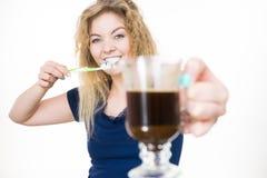拿着牙刷和咖啡的愉快的妇女 免版税图库摄影