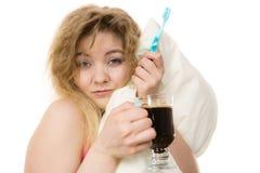拿着牙刷和咖啡的疲乏的妇女 免版税图库摄影