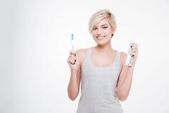 拿着牙刷和牙膏的愉快的白肤金发的妇女 图库摄影