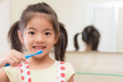 拿着牙刷的美丽的青年孩子女儿 免版税库存图片