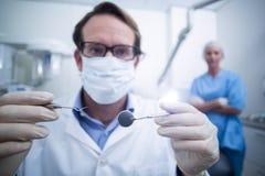 拿着牙齿工具的牙医 库存图片