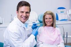 拿着牙齿模子的医生画象,当坐由患者时 免版税库存图片