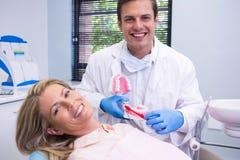 拿着牙齿模子的愉快的牙医由妇女在诊所 图库摄影