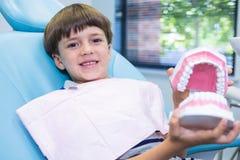 拿着牙齿模子的男孩,当坐椅子在诊所时 库存图片
