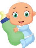 拿着牛奶瓶的男婴 免版税库存图片
