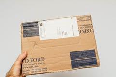 拿着牛津图书馆新闻纸板的人 图库摄影