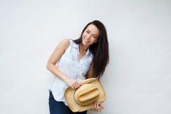 拿着牛仔帽的微笑的妇女 免版税图库摄影