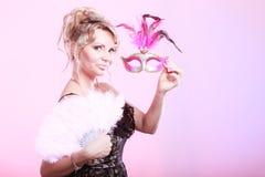 拿着狂欢节面具羽毛爱好者的妇女手中 免版税库存照片