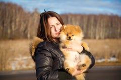 拿着狗波美丝毛狗的美丽的女孩。小品种。 免版税库存照片