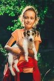 拿着狗的女孩微笑和看照相机 免版税库存图片