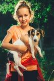 拿着狗的女孩微笑和看照相机 免版税库存照片