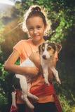 拿着狗的女孩微笑和看照相机 库存图片