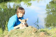 拿着狗的小男孩 图库摄影