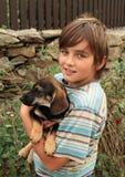 拿着狗的小男孩 免版税库存图片