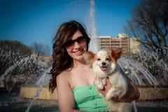 拿着狗的礼服的可爱的女孩 免版税库存图片