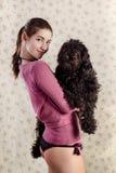 拿着狗的美丽的女孩 库存照片