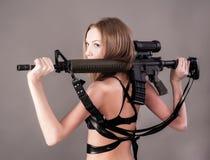 拿着狙击步枪的可爱的妇女 免版税库存图片