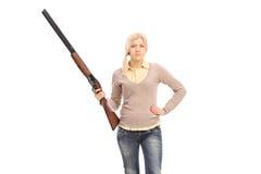 拿着猎枪的危险女孩 免版税库存照片