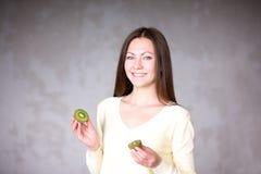 拿着猕猴桃的美丽的女孩 健康的食物 免版税库存图片