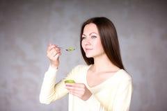 拿着猕猴桃的美丽的女孩 健康的食物 库存图片