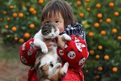 拿着猫的女孩 免版税库存图片
