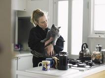 拿着猫的妇女在国内厨房里 图库摄影