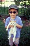 拿着猫的男孩 库存图片