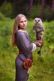 拿着猫头鹰的装甲的女孩 库存照片