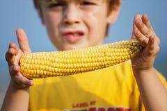 拿着玉米棒子的小男孩 免版税图库摄影