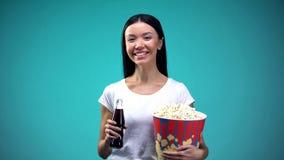 拿着玉米花和甜饮料瓶的快乐的妇女,准备好观看影片 免版税图库摄影