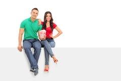 拿着玉米花的年轻夫妇供以座位在盘区 免版税库存照片