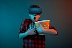 拿着玉米花的VR玻璃的害怕的男孩 免版税图库摄影