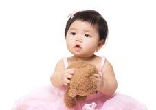 拿着玩偶的可爱的小女孩 免版税库存照片