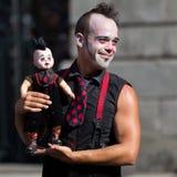 拿着玩偶的小丑。 免版税库存图片