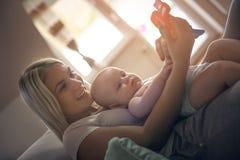 拿着玩具和使用与她的小男婴的年轻母亲 库存照片