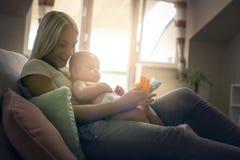 拿着玩具和使用与她的小男婴的微笑的母亲 免版税库存图片