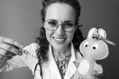 拿着玩具和使用注射器的儿科医生妇女  库存照片