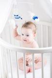 拿着玩具和坐在它的小儿床的尿布的甜婴孩 图库摄影