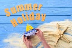 拿着玩具小船的妇女在蓝色的暑假题字之前 皇族释放例证