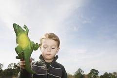 拿着玩具恐龙的男孩 免版税库存照片