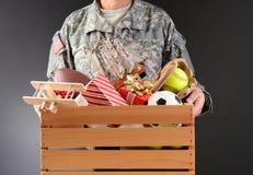 拿着玩具推进箱子的战士 免版税库存图片