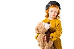 拿着玩具熊和看照相机的红色头发孩子 库存照片