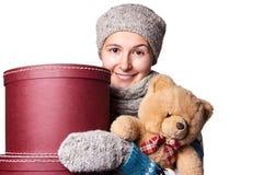 拿着玩具熊和箱子白色背景的年轻美丽的女孩 免版税库存图片