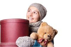 拿着玩具熊和箱子白色背景的年轻美丽的女孩 图库摄影