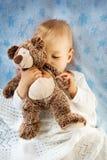 拿着玩具熊的一个岁婴孩 免版税图库摄影