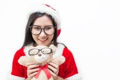 拿着玩具熊的亚裔美丽的妇女佩带圣诞老人custume的和玻璃画象  库存图片