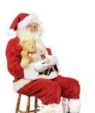 拿着玩具熊的圣诞老人 图库摄影
