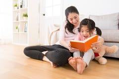 拿着玩具熊的女孩观看新的故事书 免版税库存照片